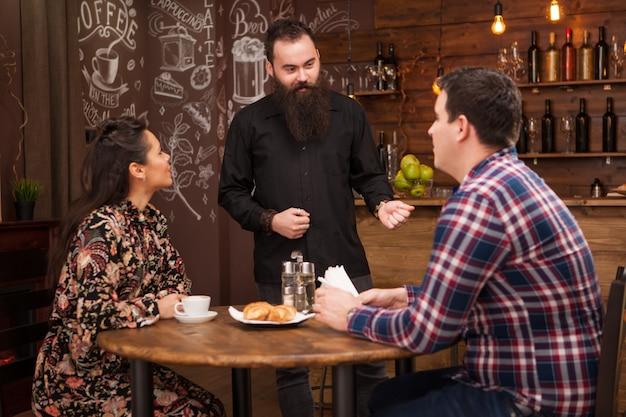 Fröhlicher bärtiger junger barmann, der im restaurant lacht und mit kunden spricht. entspannende stimmung.