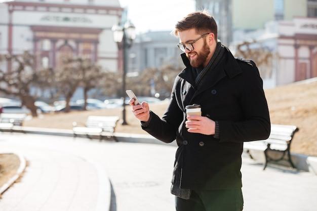 Fröhlicher bärtiger junger mann, der handy benutzt und kaffee in der stadt trinkt