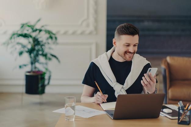 Fröhlicher bärtiger junger mann studiert drinnen mit modernen geräten schreibt notizen von der internet-website auf und macht aufzeichnungen im notebook hält smartphone-posen im gemütlichen interieur des coworking space. hipster-student