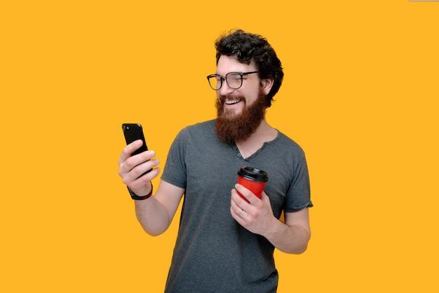 Fröhlicher bärtiger kerl benutzt ein smartphone, während er eine tasse mit kaffee auf gelb hält