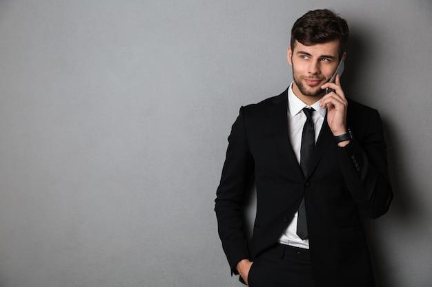 Fröhlicher bärtiger kerl im schwarzen anzug, der auf handy spricht und beiseite schaut