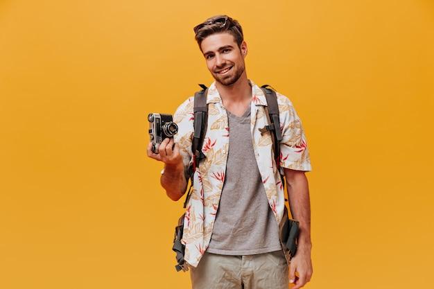 Fröhlicher bärtiger kerl in grauem t-shirt und modisch bedrucktem hemd lächelt und hält kamera an isolierter orangefarbener wand