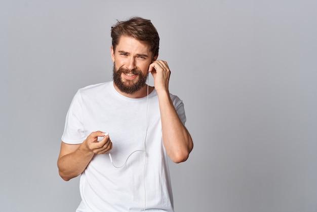 Fröhlicher bärtiger mann auf einem weißen t-shirt emotionen hält seine hand in der nähe seines gesichts