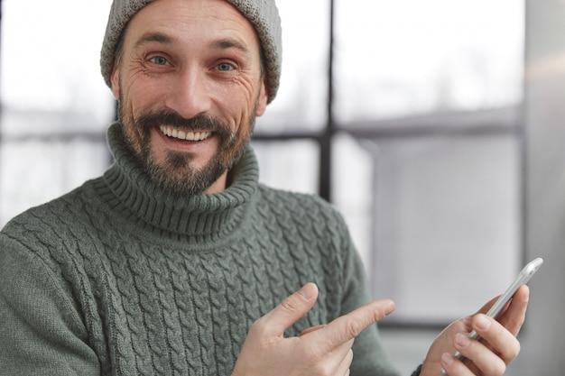 Fröhlicher bärtiger mann, der gestrickten warmen pullover und hut trägt