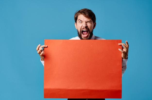 Fröhlicher bärtiger mann, der rotes banner blaues hintergrundstudio hält