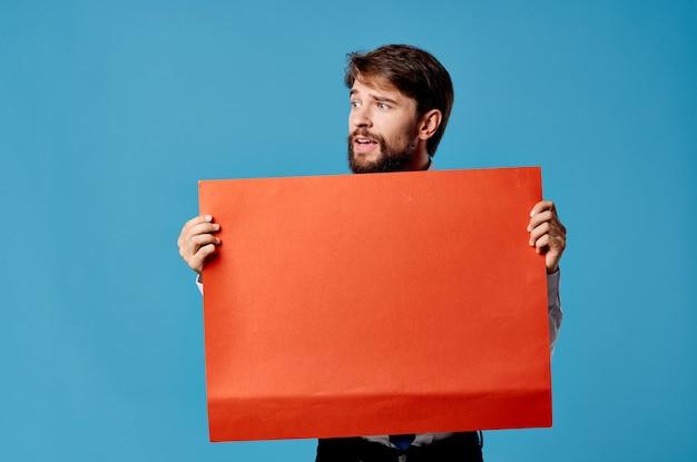 Fröhlicher bärtiger mann, der rotes banner blaues studio hält