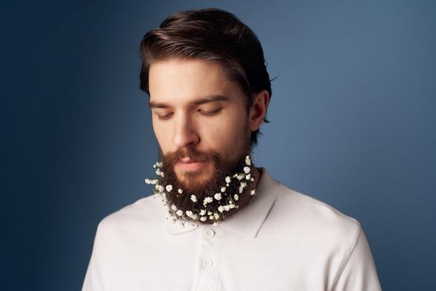 Fröhlicher bärtiger mann mit blumen in seinem modernen haarstil. foto in hoher qualität