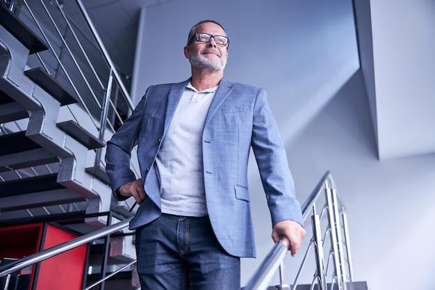 Fröhlicher bärtiger mann mit brille, der auf der treppe steht