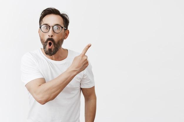 Fröhlicher bärtiger reifer mann mit brille, die aufwirft