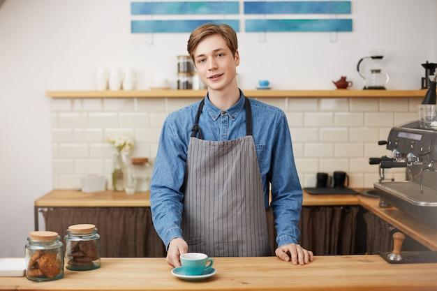 Fröhlicher barista am bartresen. dem kunden seinen bestellten kaffee geben.