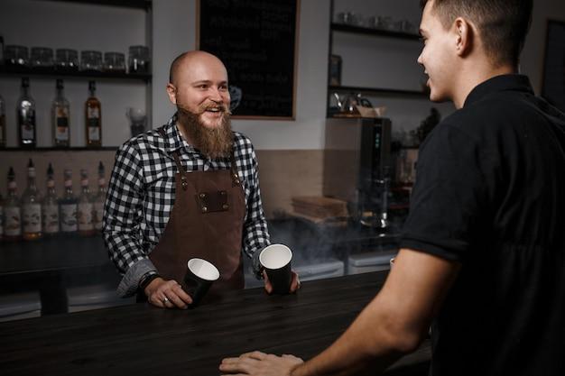 Fröhlicher barista mit bart verkauft kaffee an einen käufer in einer bar in einem modernen café