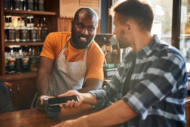 Fröhlicher barkeeper mit terminal für kontaktloses bezahlen