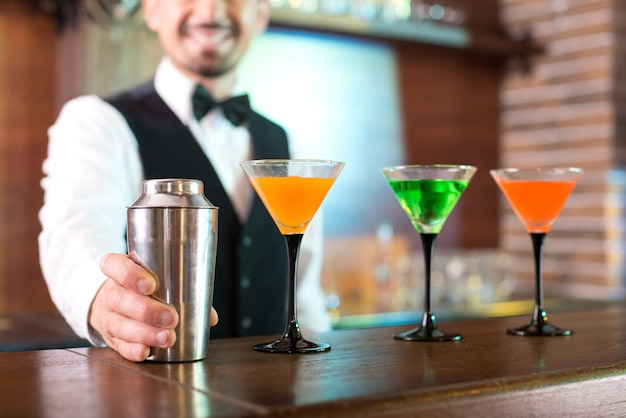 Fröhlicher barmann zeigt, wie er cocktails macht.