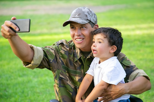 Fröhlicher behinderter militärvater und sein kleiner sohn nehmen gemeinsam selfie im park. junge sitzt auf papas schoß. kriegsveteran oder behindertenkonzept
