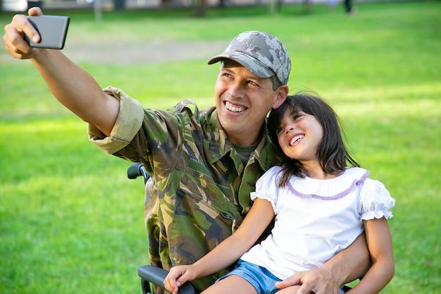 Fröhlicher behinderter militärvater und seine kleine tochter nehmen gemeinsam selfie im park. mädchen sitzt auf papas schoß. kriegsveteran oder behindertenkonzept