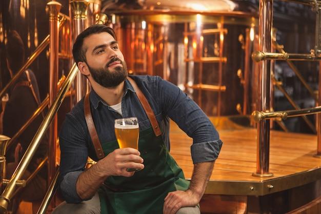Fröhlicher biermacher, der nahe bierbehältern in der produktionsfabrik sitzt