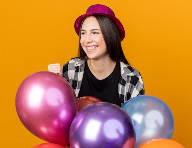 Fröhlicher blick auf die seite junges schönes mädchen mit partyhut, das hinter luftballons steht, isoliert auf oranger wand