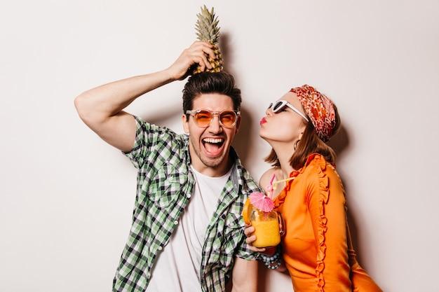 Fröhlicher brünetter mann mit heller sonnenbrille hält ananas auf dem kopf, während seine freundin ihn auf die wange küsst.