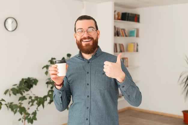Fröhlicher büroangestellter, der daumen oben und kaffeetasse zeigt, um zu gehen