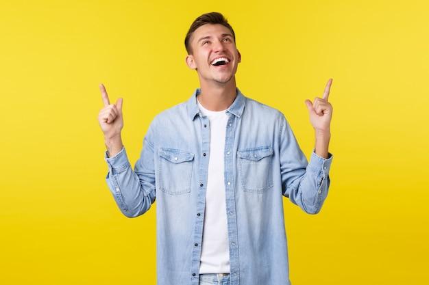 Fröhlicher, charismatischer blonder kerl, der laut lacht und weiße zähne lächelt, mit den fingern auf lustige werbebanner schaut und darauf zeigt, sommerangebote und rabatte für kurse genießt.