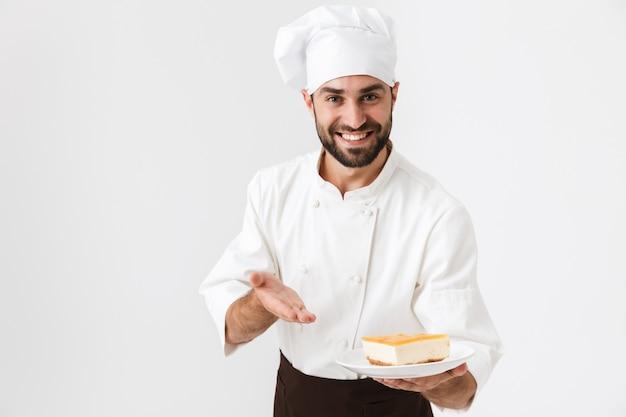Fröhlicher chef in kochuniform lächelt und hält teller mit stück käsekuchen isoliert über weißer wand