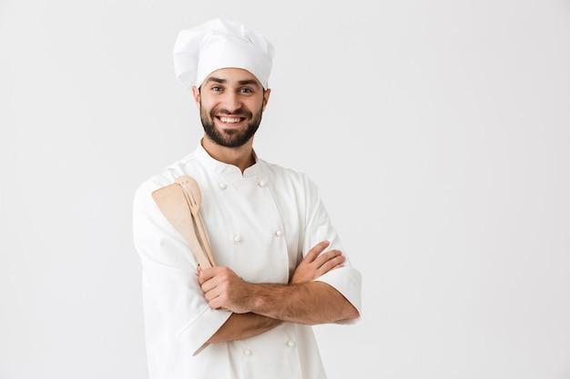 Fröhlicher chefmann in kochuniform, der lächelt, während er hölzerne küchenutensilien isoliert über weißer wand hält?