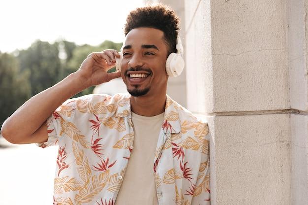Fröhlicher cooler bärtiger mann in blumenhemd und beigem t-shirt lächelt aufrichtig, lehnt sich an die wand und hört musik über kopfhörer