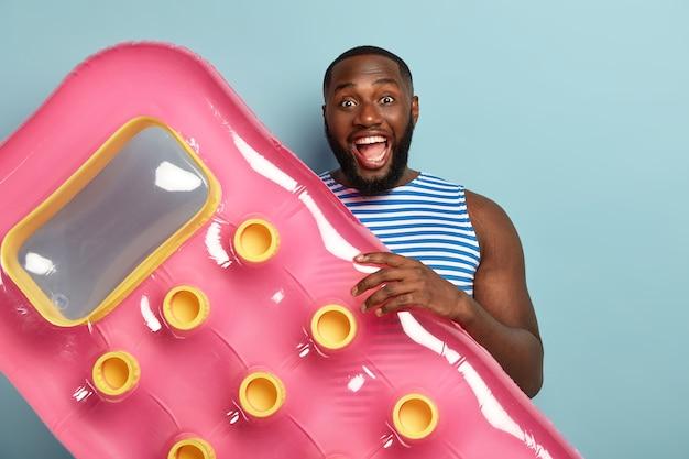 Fröhlicher dunkelhäutiger männlicher urlauber hält rosa aufgeblasene matratze, bereitet sich auf das schwimmen vor, lacht freudig