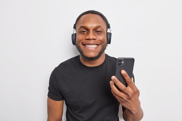 Fröhlicher dunkelhäutiger mann lächelt angenehm, hört gerne musik von der playlist hält smartphone und verwendet drahtlose kopfhörer