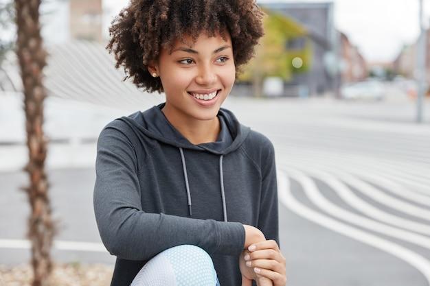 Fröhlicher dunkelhäutiger teenager mit charmantem lächeln, lässig gekleidet, genießt freizeit
