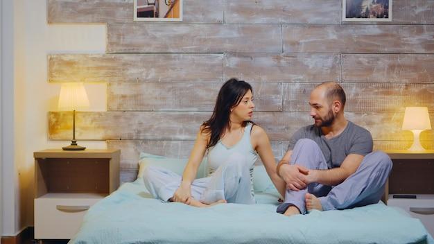 Fröhlicher ehemann und ehefrau, die pyjamas tragen und ein gespräch führen. glückliche ehe.