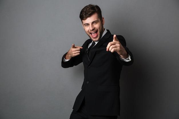 Fröhlicher emotionaler junger mann im anzug, der mit zwei fingern auf sie poitet,