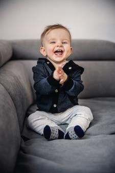 Fröhlicher entzückender lachender kleiner junge, der mit seinen händen klatscht und auf sofa sitzt.