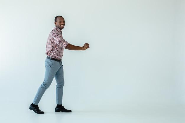 Fröhlicher erwachsener afroamerikanischer mann, der einen wagen beim einkaufen schiebt