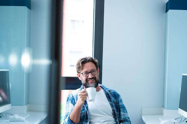 Fröhlicher erwachsener bärtiger mann, der im büro sitzt, lächelt und genießt eine pause von der online-arbeit - menschen und job-lifestyle - blaue farben - hübscher reifer mann mit brille und kaffee - moderner lebensstil