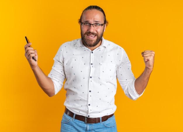 Fröhlicher erwachsener gutaussehender mann mit brille, der ein handy hält und eine ja-geste macht