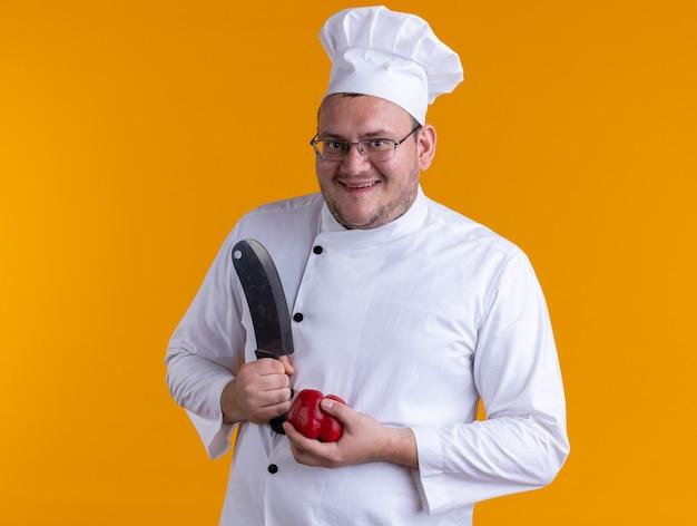 Fröhlicher erwachsener männlicher koch in kochuniform und brille mit hackmesser und pfeffer, der die kamera einzeln auf orangefarbenem hintergrund betrachtet
