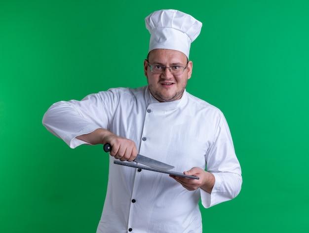 Fröhlicher erwachsener männlicher koch mit kochuniform und brille, der auf das schneidebrett blickt, das mit einem messer auf der grünen wand isoliert ist?