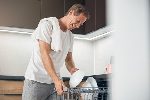 Fröhlicher erwachsener mann, der ein lächeln auf seinem gesicht behält, während er zu hause teller in der spülmaschine anschaut