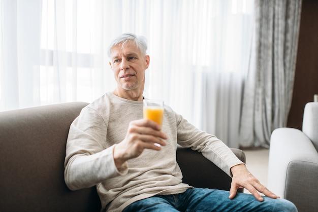 Fröhlicher erwachsener mann, der zu hause auf der couch sitzt und frischen saft trinkt. reife männliche person in jeans entspannen im sessel