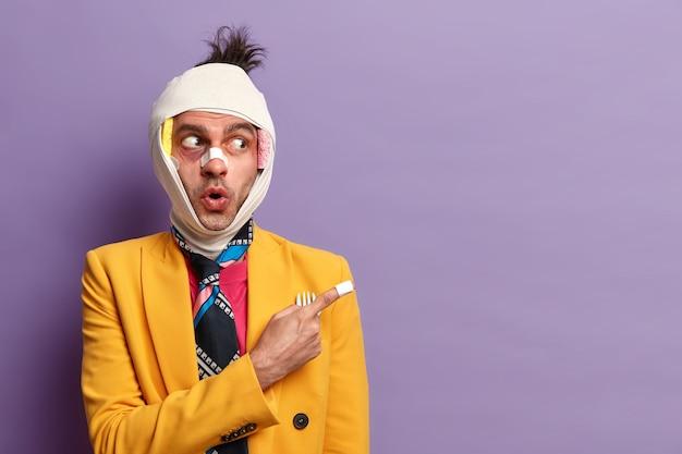 Fröhlicher erwachsener mann hat ein kopftrauma, eine gebrochene nase und blaue flecken unter den augen