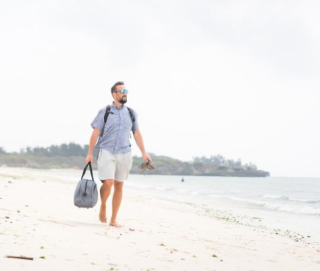 Fröhlicher erwachsener mann mit tasche, die spaß am tropischen strand hat
