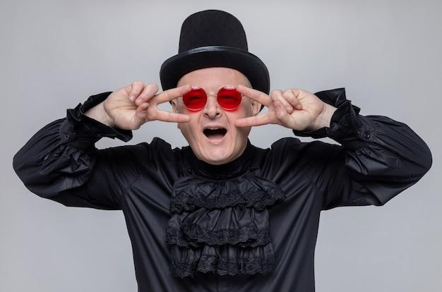 Fröhlicher erwachsener mann mit zylinder und sonnenbrille im schwarzen gothic-hemd, der das siegeszeichen gestikuliert