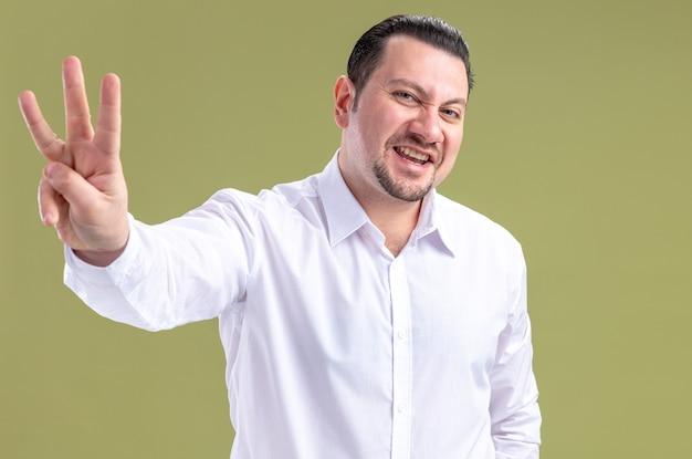 Fröhlicher erwachsener slawischer geschäftsmann, der drei mit den fingern gestikuliert