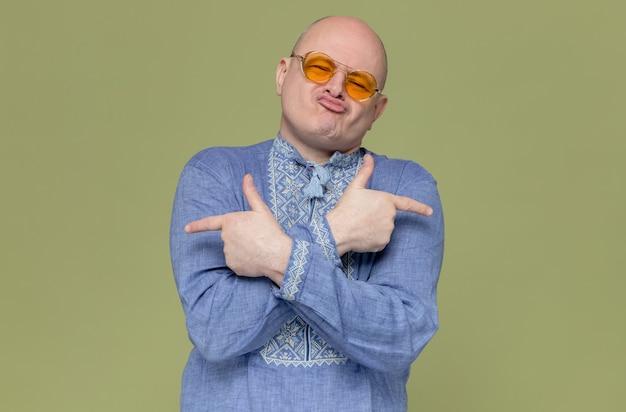Fröhlicher erwachsener slawischer mann im blauen hemd mit sonnenbrille, die auf die seiten zeigt