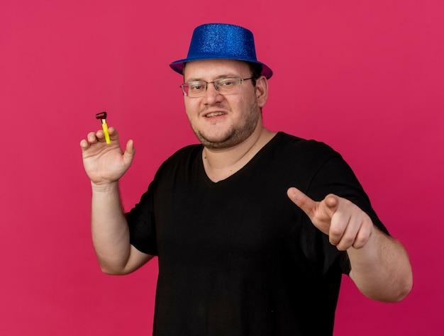 Fröhlicher erwachsener slawischer mann in optischer brille mit blauem partyhut hält partypfeife, die auf die kamera zeigt