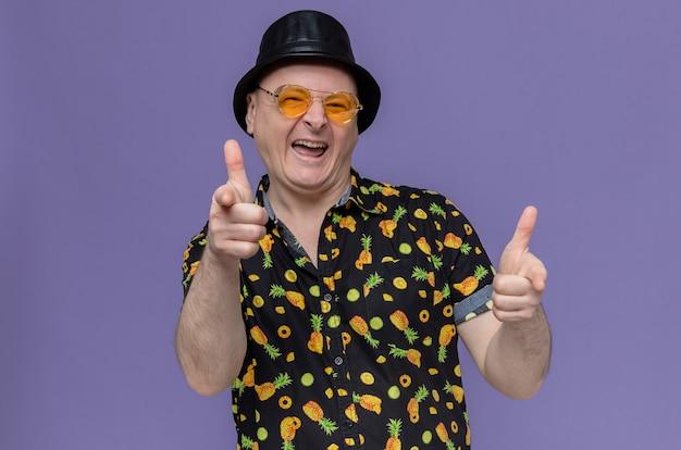 Fröhlicher erwachsener slawischer mann mit schwarzem hut, der eine sonnenbrille trägt, die nach vorne zeigt