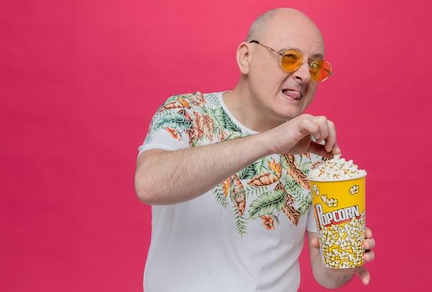 Fröhlicher erwachsener slawischer mann mit sonnenbrille, der popcorn-eimer hält