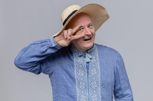 Fröhlicher erwachsener slawischer mann mit strohhut und im blauen hemd, der siegeszeichen gestikuliert