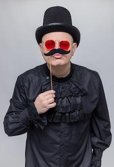 Fröhlicher erwachsener slawischer mann mit zylinder und sonnenbrille in schwarzem gothic-hemd, der einen falschen schnurrbart am stock hält